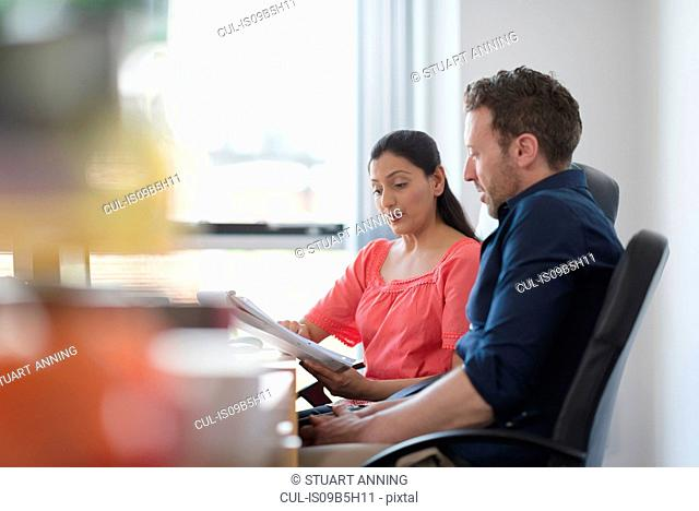 Colleagues in discussion at office desk