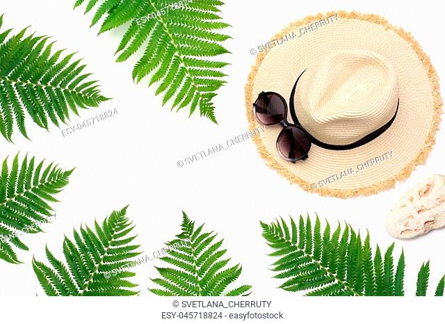 Tropical vacation. Straw beach sunhat, sun glasses, leaf of fern on white background. Top view with copy space. Summer concept
