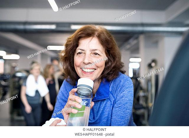 Fit senior woman resting after working out in gym