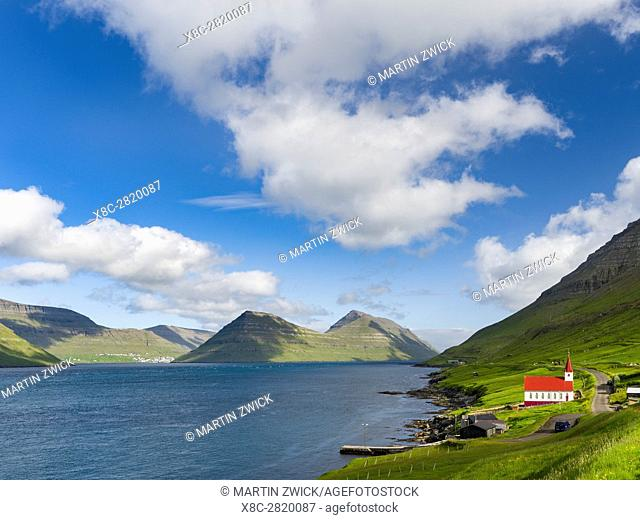 The church in village Husar on Kalsoy, in the background the island of Bordoy and Klaksvik. Nordoyggjar (Northern Isles) in the Faroe Islands