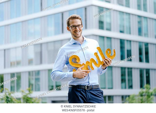 Young businessman holding smile sign