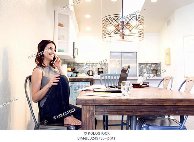 Caucasian woman sitting at table near laptop talking on cell phone