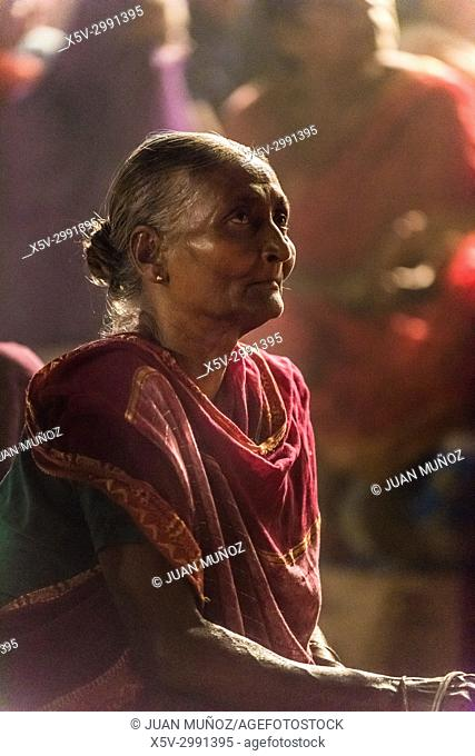Elderly woman in Ganga Aarti ceremony on the ghats of the Ganges, Benares, Varanasi, Uttar Pradesh, India