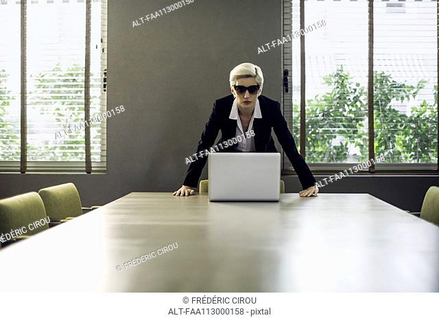 Woman in suit leaning against table looking at camera