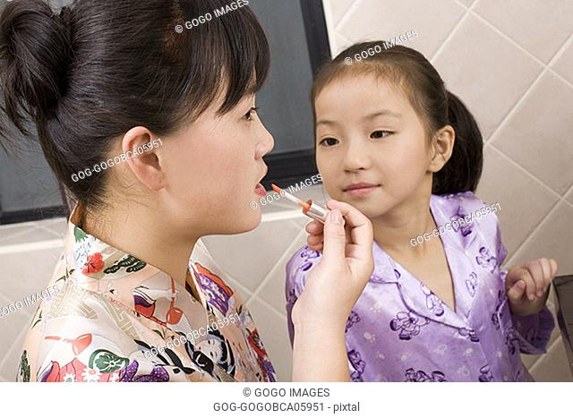 Mother applying lipstick as daughter watches