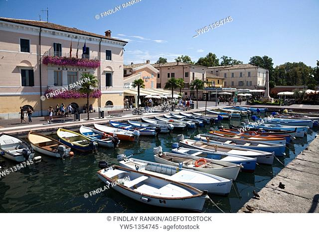 Small boats used by local fishermen tied up in the marina at Bardolino, Lake Garda, Italy