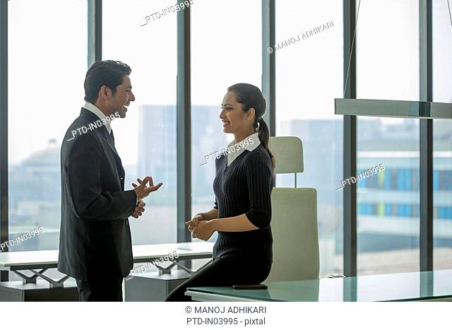 India, Businessman talking to woman sitting on desk
