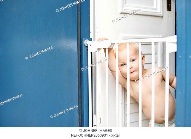 Baby boy looking through gate