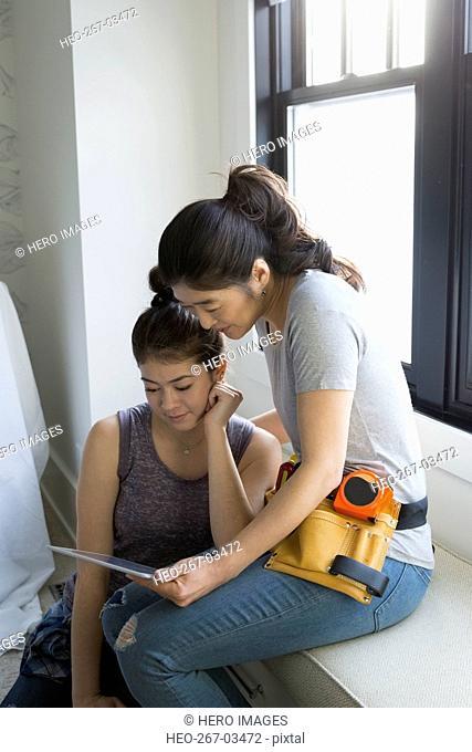 Mother and teenage daughter researching DIY digital tablet
