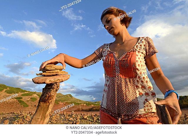 Young woman building a stone sculpture in Cala Pregonda, Menorca