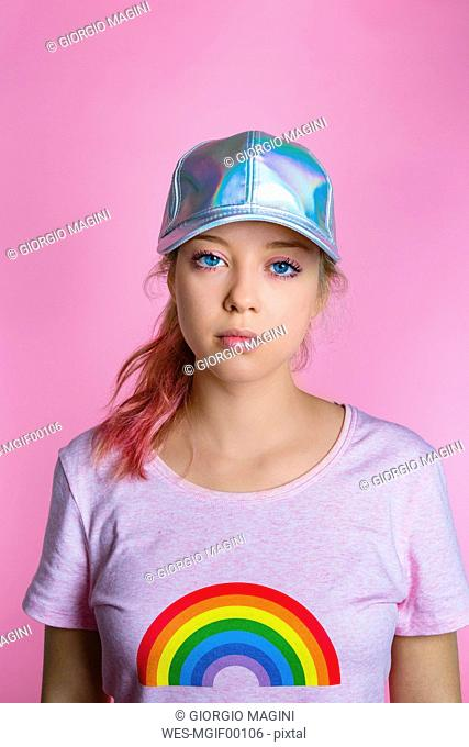 Portrait of stylish young woman wearing basecap in front of pink background