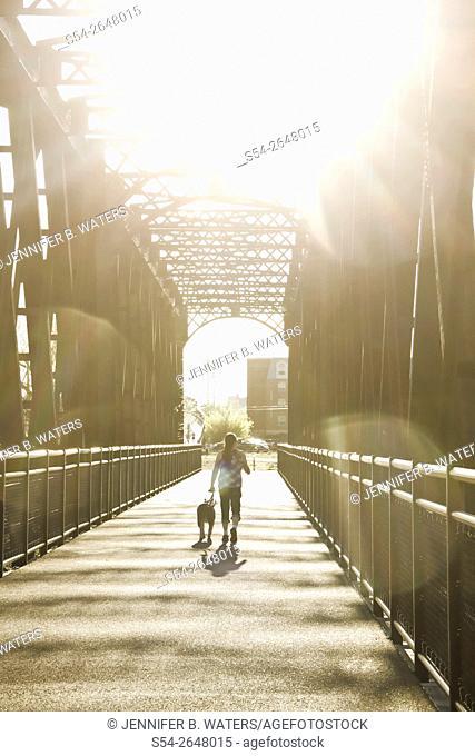 A woman and her dog on a trail on an old railroad bridge by the Spokane River in Spokane, Washington, USA