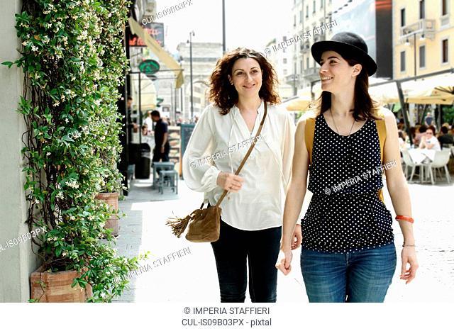 Two women strolling along city street, Milan, Italy