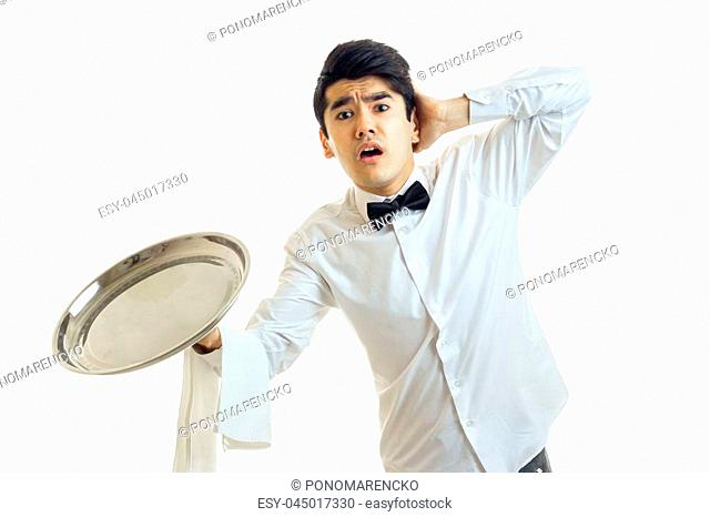 the young waiter with an empty tray for cupboards opened his mouth and kept the ball for a head isolated on white background close-up