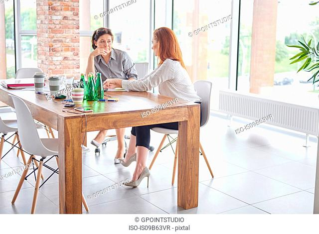 Women sitting at dining table chatting