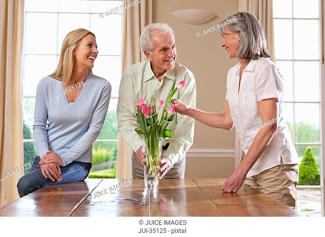 Smiling parents and daughter arranging tulips in vase on dining room table