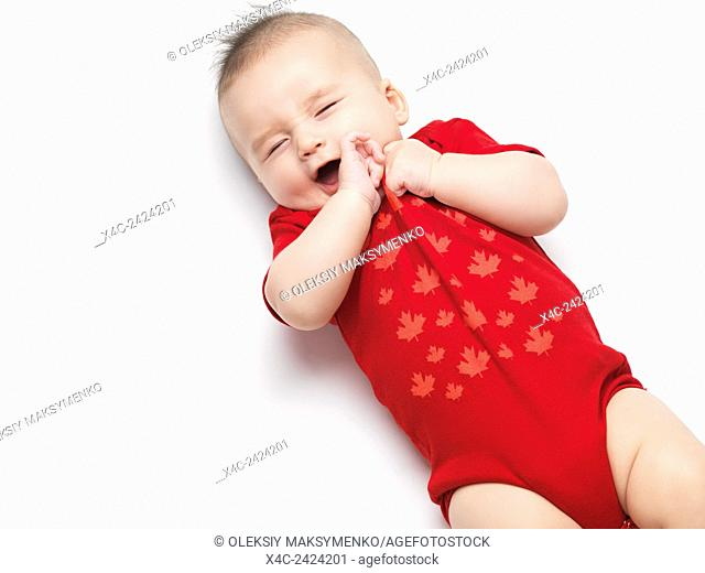 Happy cute yawning four month old baby boy wearing red body suit. Isolated on white background