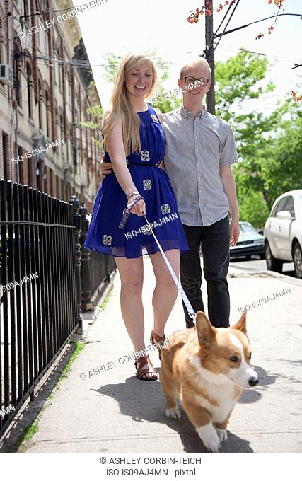 Young couple taking corgi dog for a walk along street