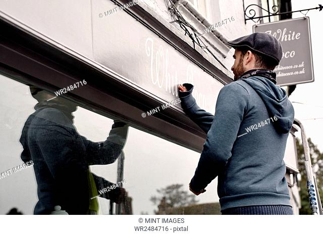 A man on a ladder fixing a painted name sign onto a bracket on a shopfront