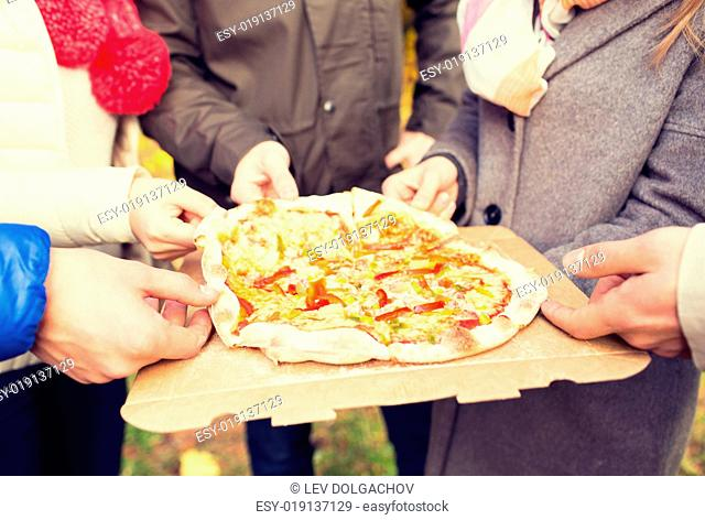 friendship, junk food and people concept - close up of friends hands eating pizza from cardboard box outdoors