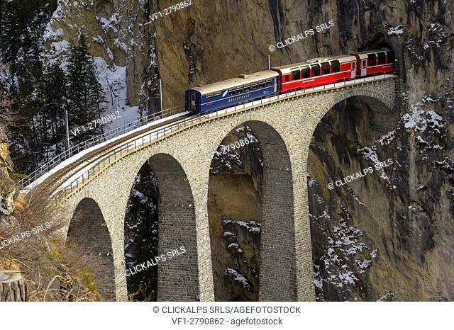 Red Bernina Express train and the Landwasser viaduct. Engadine, Switzerland, Europe