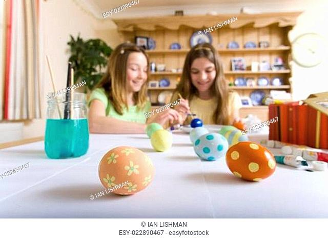 Two young girls decorating Easter eggs