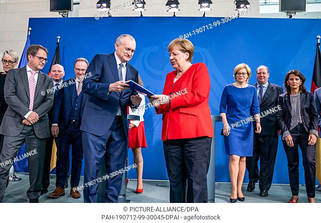 12 July 2019, Berlin: Federal Chancellor Angela Merkel (CDU) receives the special report on CO2 pricing from the Chairman of the Council of Experts, Christoph M