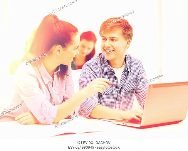 education, technology and internet concept - two smiling students with laptop computer and notebooks at school