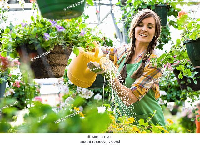 Caucasian woman watering plants in nursery