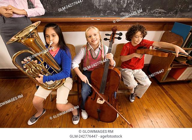 Three students playing musical instruments in a classroom