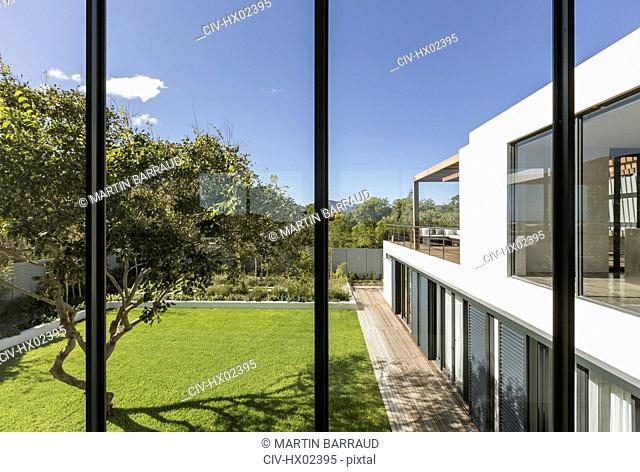 View from windows of sunny modern luxury home showcase exterior with yard and tree