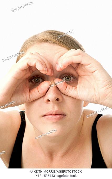 a young caucasian woman looking through her hands shaped like binoculars, uk