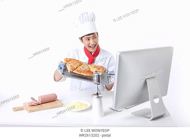 Portrait of young male cook showing pizza broadcasting