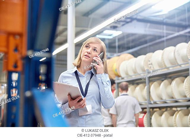 Female supervisor with clipboard talking on cell phone in fiber optics factory
