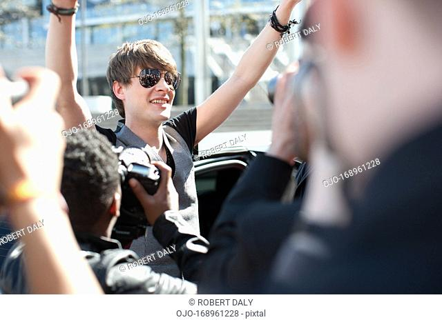 Celebrity emerging from limo towards paparazzi