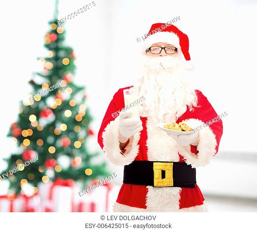christmas, holidays, food, drink and people concept - man in costume of santa claus with glass of milk and cookies over living room with tree