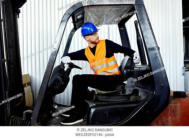 Worker on forklift in factory turning round