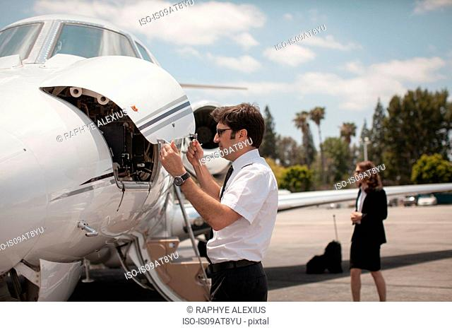 Male pilot checking private jet at airport