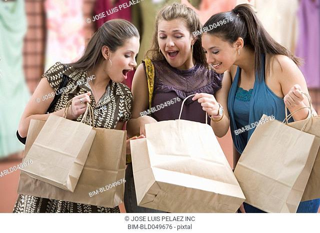 Multi-ethnic teenaged girls looking in shopping bag