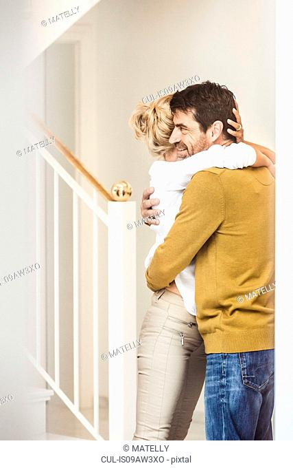 Mature couple at home, standing beside staircase, hugging