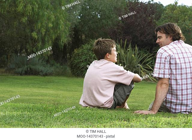 Father and son 10-12 sitting on lawn and talking