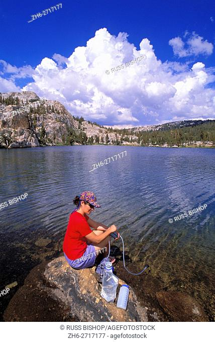 Woman purifying drinking water on the shore of Boothe Lake, Yosemite National Park, California USA