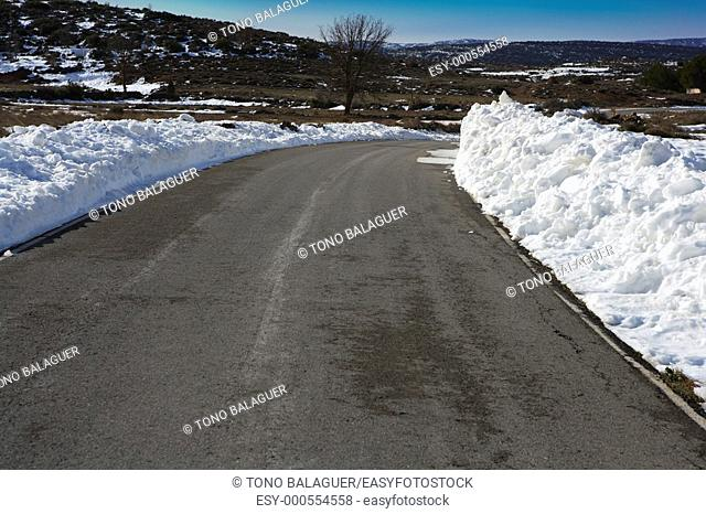 asphalt road curve with snow in both side borders