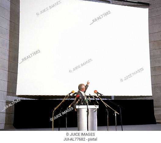 Businessman at podium pointing at large projection screen