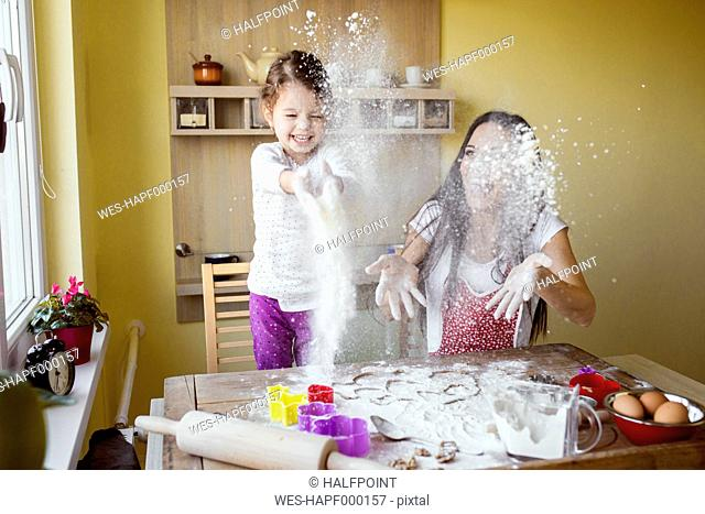 Mother and her little daughter throwing flour in the air at the kitchen