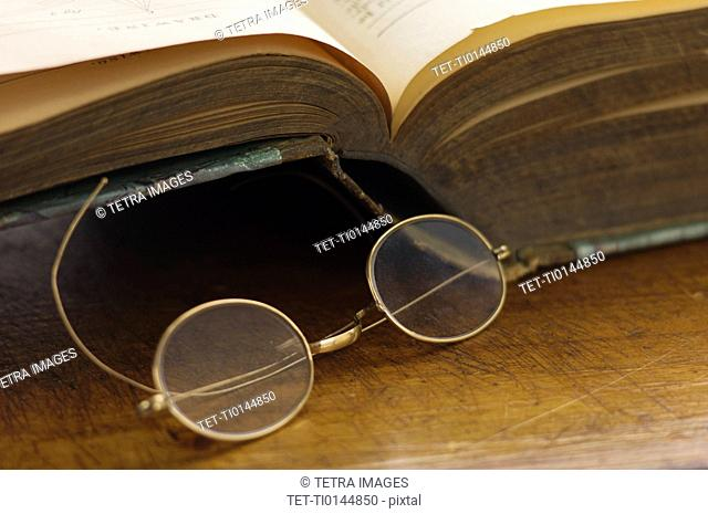 Close up antique round glasses and open book