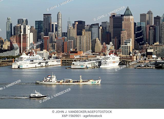 Boats on the Hudson River passing docked cruise ships  The workboat in the foreground is a NYC Department of Environmental Protection sludge boat which brings...