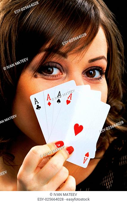 Young woman holding four aces in front of her face