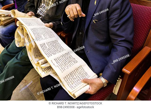Jewish man holding the Scroll of Esther magilla in a synagogue in Casablanca during the Celebration of Purim