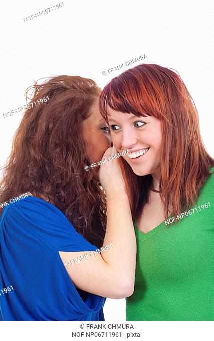 two young women whispering gossip - isolated on white
